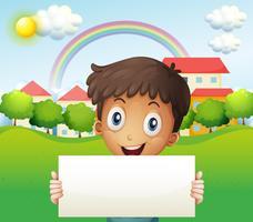 Een glimlachende jongen die een leeg karton houdt