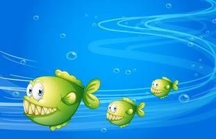 Drie groene piranha's onder de zee
