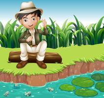 Een jongen zit op een bos aan de rivieroever