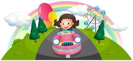 Een jong meisje die in een roze auto met ballons berijden