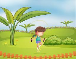 Een meisje springtouw spelen in het park