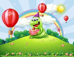 Een gelukkig groen monster dat zijn verjaardag viert bij de heuveltop