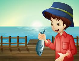 Een visser die een vis houdt bij de zeehaven