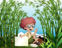 Een jonge jongen die een leeg uithangbord in het bamboeregenwoud houdt
