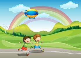 Kinderen lopen met een luchtschip erboven