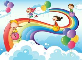 Een groep kinderen die aan de hemel spelen met een regenboog