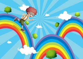 Een jongen die aan de top van de regenboog loopt