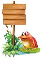 Een kikker boven een waterlelie naast een houten bord