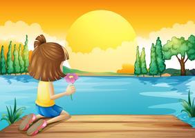 Een meisje dat een bloem houdt die bij de rivier onder ogen ziet
