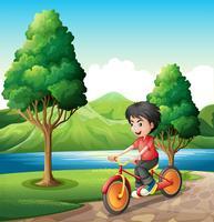 Een jongen die op de rivieroever fietst