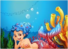 Een zeemeermin in de buurt van de koraalriffen