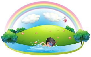 Een jongen die bij het strand dichtbij de heuvel zwemt