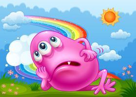 Een vermoeide roze monster op de heuveltop met een regenboog aan de hemel vector