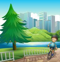 Een jongen die over de hoge gebouwen langs de rivier fietst