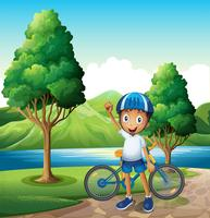 Een lachende jonge jongen op de rivieroever met zijn fiets