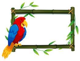 Papegaai op bamboeframe vector