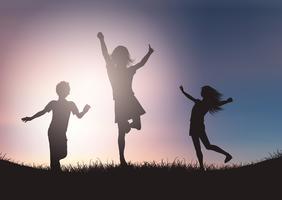Silhouetten van kinderen die tegen zonsonderganghemel spelen