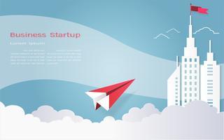 Leidingsconcept, Rood vliegtuig en wit architecturaal de bouwlandschap met een vlag op de hoogste, Blauwe hemelachtergrond.