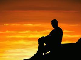 Silhouet eenzame man alleen zittend bij schemering.