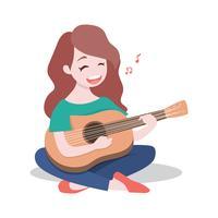 Het gelukkige jonge meisje die de gitaar spelen en zingt een lied, op witte achtergrond wordt geïsoleerd