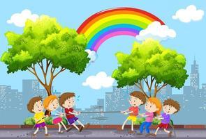 Kinderen die touwtrekwedstrijd spelen met stadsgezicht