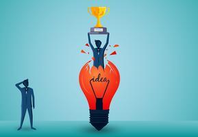 Bedrijfsmens die een winnaarstrofee houden over zijn hoofd die van een gloeilamp uitbreken