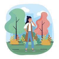 Jonge vrouw die op smartphone in park spreekt vector