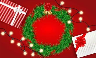 Kerst ontwerp met verlichting, krans en geschenken op rood