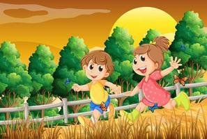 Kinderen spelen in het bos in de buurt van de houten hek