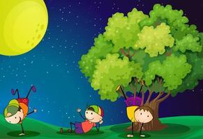 Drie kinderen spelen in de buurt van de boom onder de fullmoon