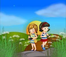 Twee meisjes op de heuveltop met behulp van hun mobiele telefoons vector