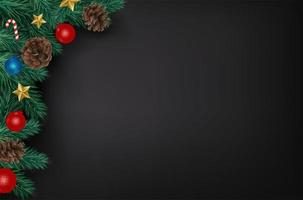 Kerstboomtakken en ornamenten die zwarte achtergrond grenzen