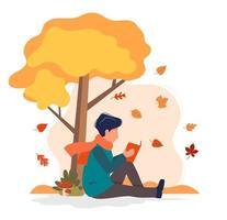 man leesboek onder boom in de herfst