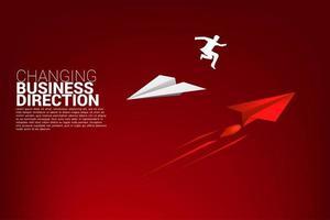 zakenman springen van het ene papieren vliegtuig naar het andere