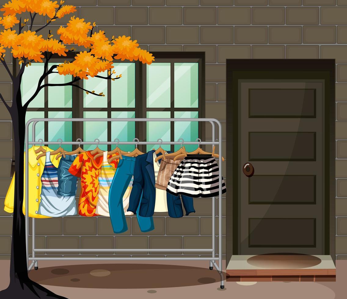 viele Kleider hängen an einem Kleiderständer vor der Hausszene vektor