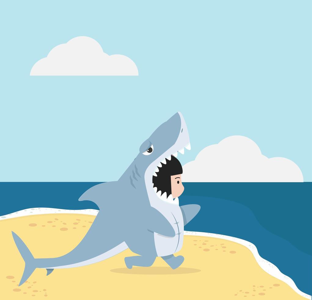 ungen i hajdräkt går på stranden vektor