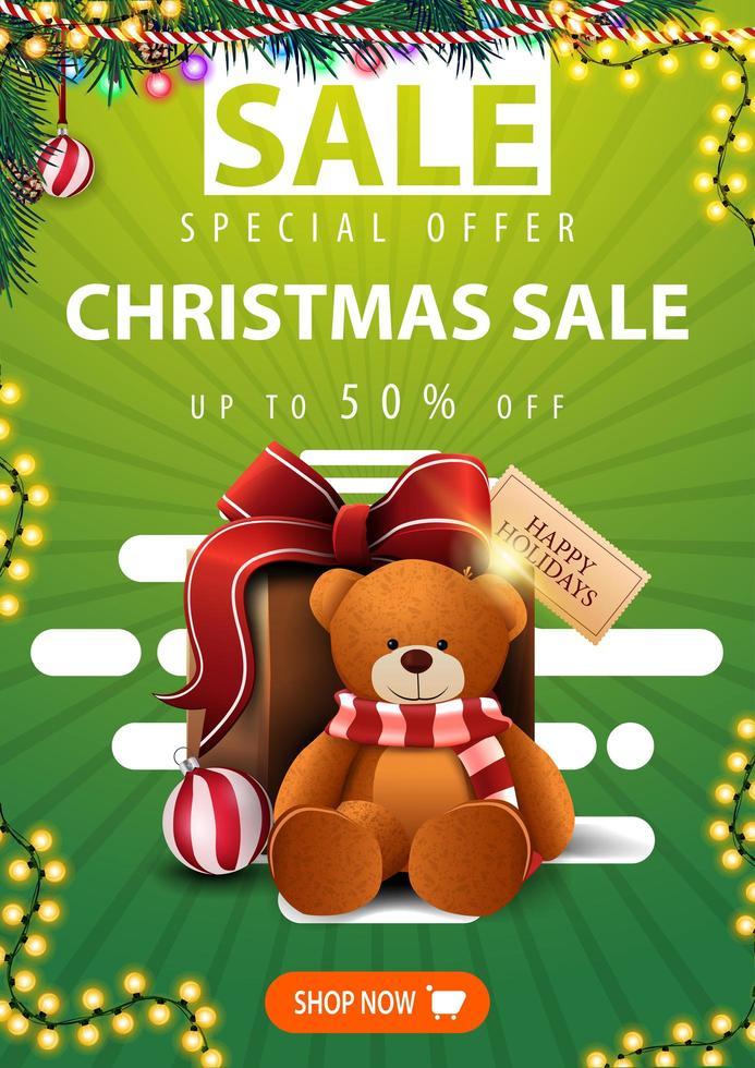 Sonderangebot, Weihnachtsverkauf, bis zu 50 Rabatt, grünes vertikales Banner mit Weihnachtsbaumzweigen, Girlanden, Knopf und Geschenk mit Teddybär vektor