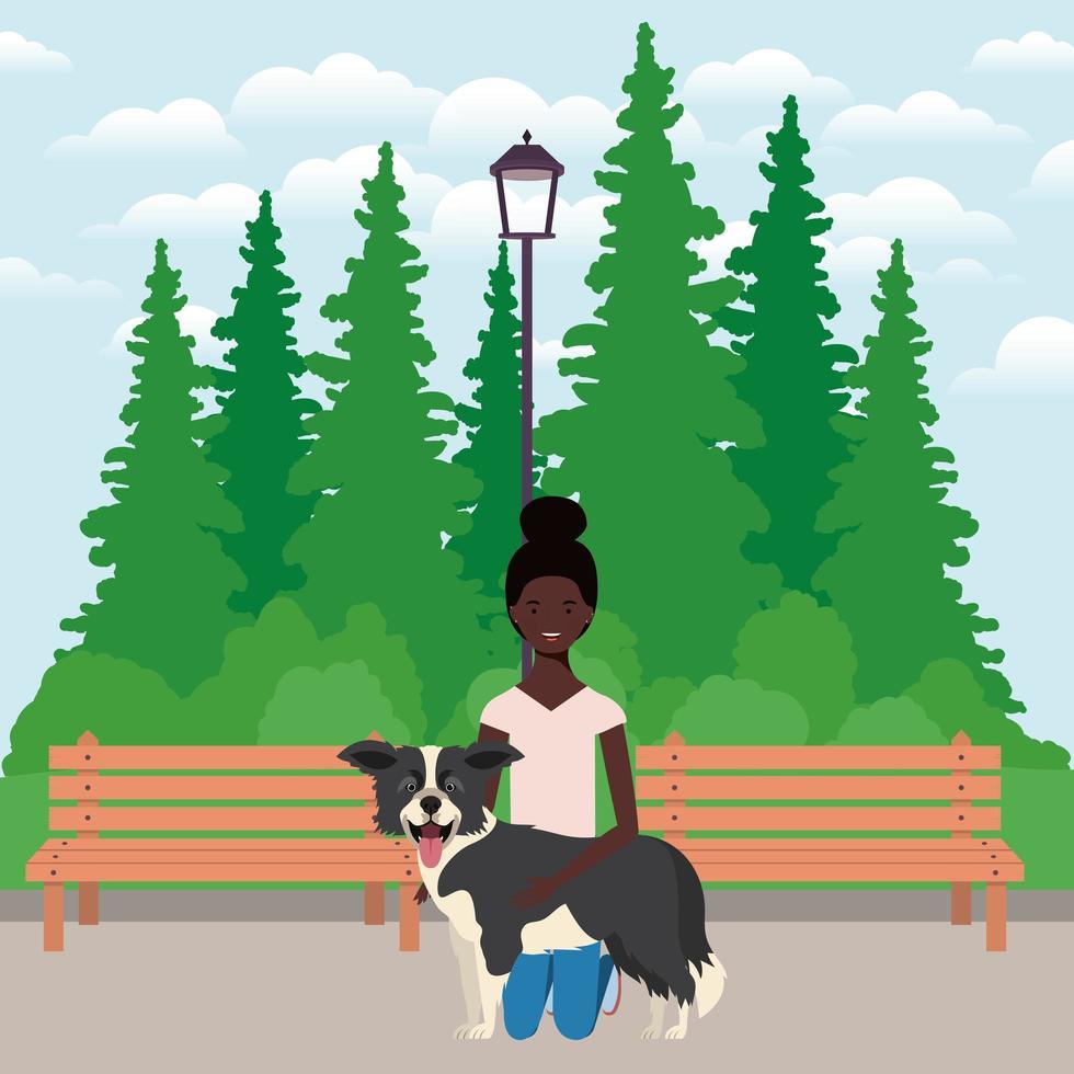 junge Afro-Frau, die niedlichen Hund auf dem Feld anhebt vektor