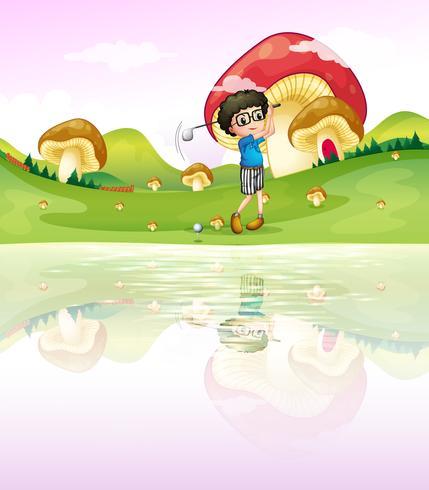 Ein Junge, der Golf am Flussufer spielt vektor