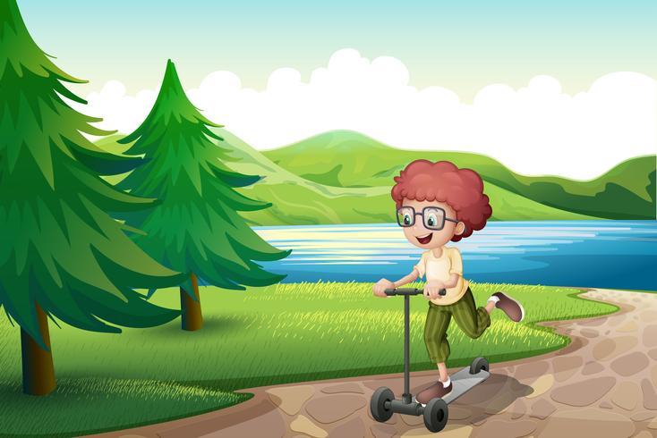 Ein Junge, der mit seinem Roller nahe dem Fluss spielt vektor