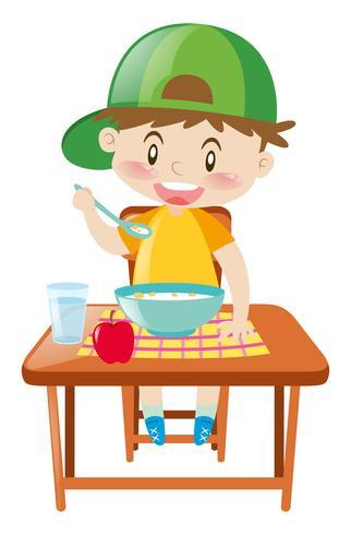 Kleiner Junge am Speisetische Frühstück essend vektor