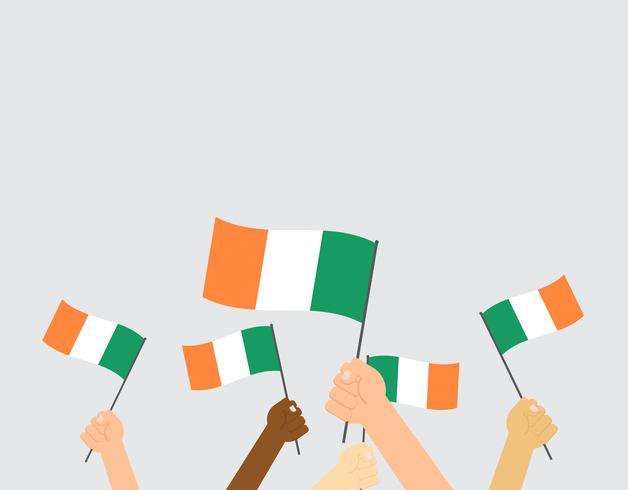 Vector Illustration von den Händen, die Irland-Flaggen halten, die auf grauem Hintergrund lokalisiert werden