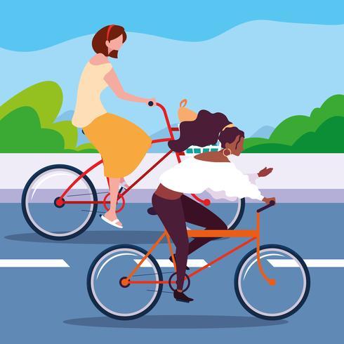 två kvinnor som cyklar på vägen vektor