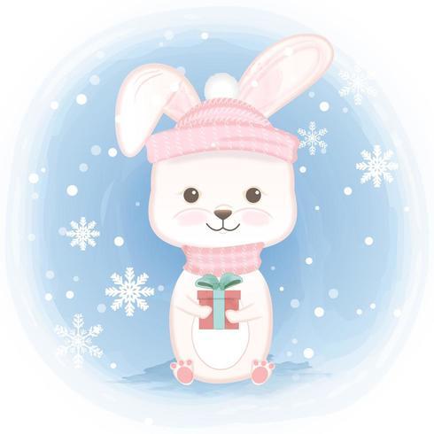 Kaninchen, das Geschenkbox und Schneeflocke hält vektor