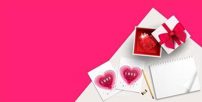 Draufsicht des Geschenks mit juwelenbesetztem Herzen auf rosa