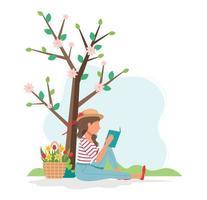 Frau liest Buch unter dem Baum