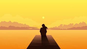 einsame Mädchenschattenbild, die auf Pier bei Sonnenuntergang sitzt