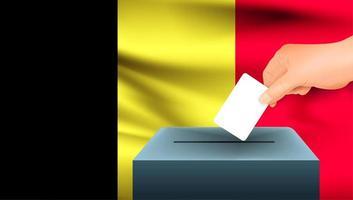 Hand, die Stimmzettel in Box mit belgischer Flagge setzt