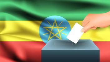 Hand, die Stimmzettel in Box mit äthiopischer Flagge setzt