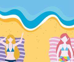kvinnor vilar på handdukar i sanden